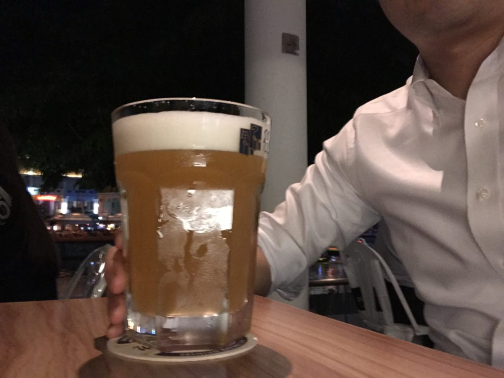 自己紹介の写真(シンガポールのマリーナ近くのバーでビールを飲んでいる)